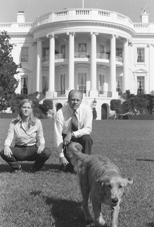 """President Gerald Ford and his daughter Susan sit on the White House lawn October 6, 1974, watching """"Liberty,"""" a golden retriever, given to the president by his daughter and White House photographer David Kennerly."""