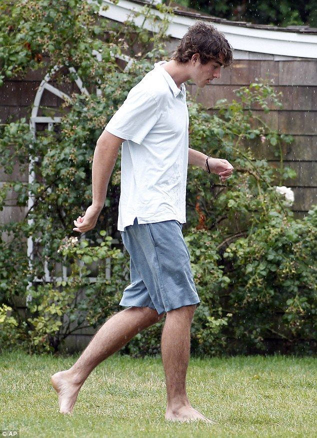 Conor Kennedy tries to stay dry as he walks on the Kennedy Compound before his father's wedding to actress Cheryl Hines, 8/2/14