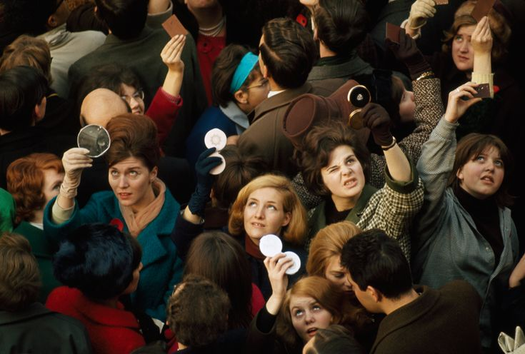 Women use compact mirrors in packed crowd to catch sight of the queen in London, June 1966. / James P. Blair