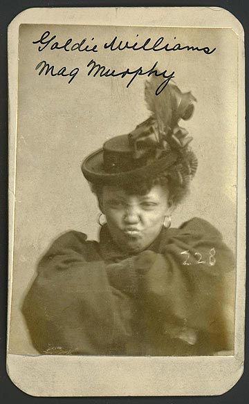 On January 29, 1898, Goldie Williams was arrested by the Omaha Police for vagrancy. At the time of her arrest, she was described as 5 feet tall and 110 pounds, her left index finger was broken and she had a cut below her right wrist. Williams listed her home as Chicago and occupation as a prostitute. In her mug shot she is seen sitting defiantly with her arms crossed sporting an elaborate hat and large hoop earrings.