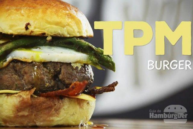 A receita completa do TPM Burger leva pão brioche, bacon crocante, queijo cheddar, cebola caramelizada, ovo e aspargos. - Sanduba Insano