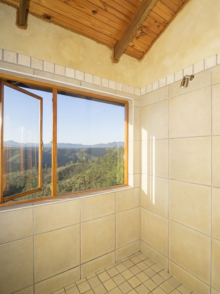 The large shower at Cliffhanger Cottage looking out at the view of the forest and mountains.