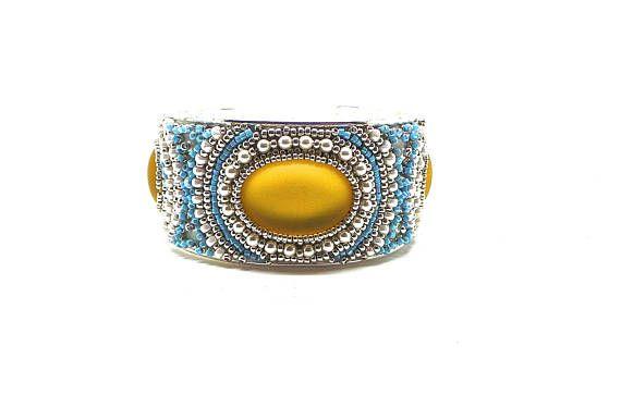 Ce bracelet jaune est réalisé avec des cabochons lunasoft jaune des micros perles de verre dorées et des perles en cristal transparentes ,argent et blanches . monté sur un support de bracelet rigide , il convient parfaitement à tous les poignets.  VOUS POUVEZ CHOISIR LA COULEUR DE VOTRE CHOIX , UN DÉLAI D UNE SEMAINE SERA NÉCÉSSAIRE À LA RÉALISATION , ces bracelets brodés me demande un trentaine dheures de travail cest une création unique , je livre GRATUITEMENT en colissimo suivi , et…