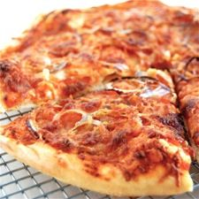 "Sourdough pizza crust? Well, why not? For one thing, this crust can go from quite sour to ""can't even tell it's sourdough,"" depending on how recently you've fed your starter. And even if you want very little (or no) tang, the vigor of the starter enhances the pizza dough's rise."
