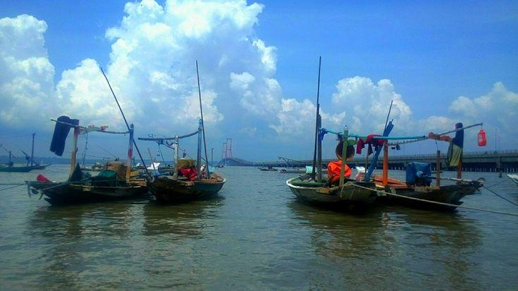 Boats on the shore of Kenjeran with background of Suramadu bridge