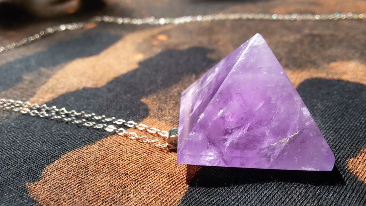 Carved from stunning purple amethyst this 2.8cm square pyramid has been mounted on a silvertone back-bail. The pyramid shape is excellent at drawing all energy around it up into the higher realms & focusing directly, precisely to a point.