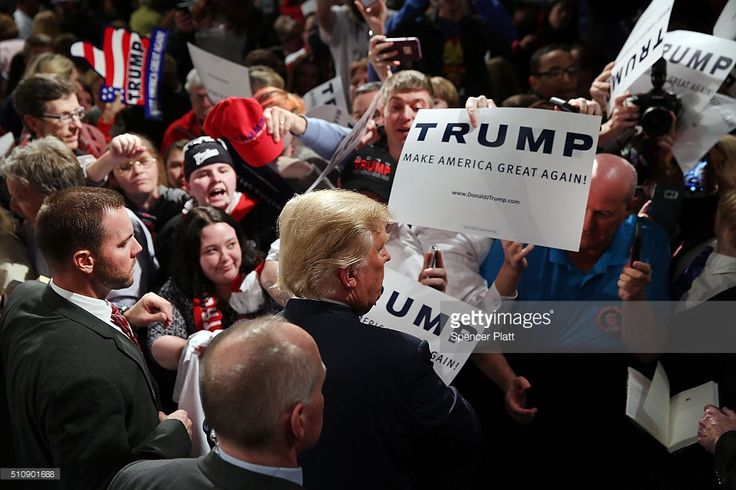 Republican presidential candidate Donald Trump signs autographs after speaking on February 17, 2016 in Sumter, South Carolina. Despite attacks from his fellow candidates about his shifting positions, Trump is still ahead in South Carolina polls only days away from the primary.