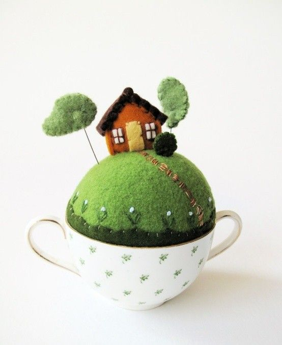 teacup to pincushion. Could attach needle-sharpener (fabric bag filled with emery sand) to handle, or fill the little house with emery sand. The cup underneath could hold small accessories. A cup holder.