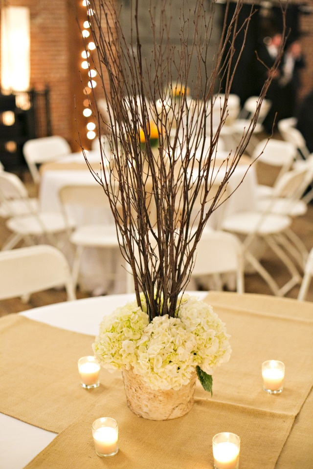 Morgan chose two centerpieces for her guest tables. Centerpiece two contained birch branches and white hydrangea in a birch container with a classic white linen, burlap runners, and votive candles   by Dorothy McDaniel's Flower Market & Ann Wade Parrish Photography