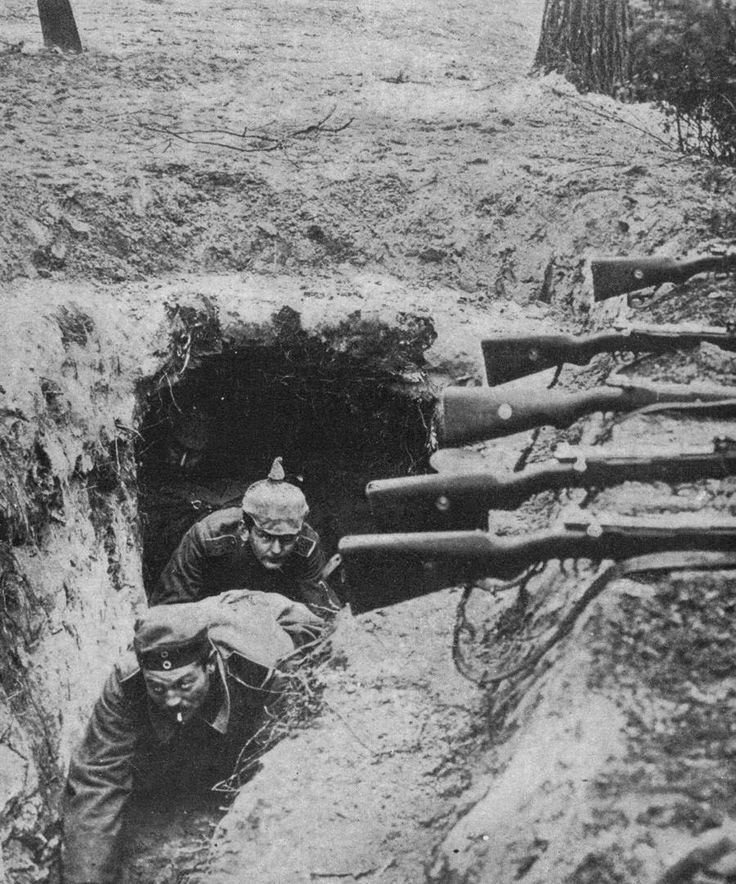 German Soldiers crawl out from a bunker into a trench. Where and when this image was taken are unknown, though the helmet depicts a Prussian regiment.