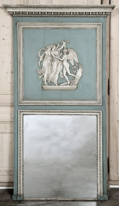 Antique French Louis XVI Trumeau. Almost seven feet in height, this antique Neoclassical trumeau will surely impress! Featuring its original pastel painted two-tone finish that has achieved a superlative patina over the past century, it boasts a generous mirror below and a stunning relief panel above that depicts a whimsical scene from mythology wherein a goddess who appears to be Diana is coming to the aid of a friend who is the object of Cupid's attentions.    Circa 1880s.