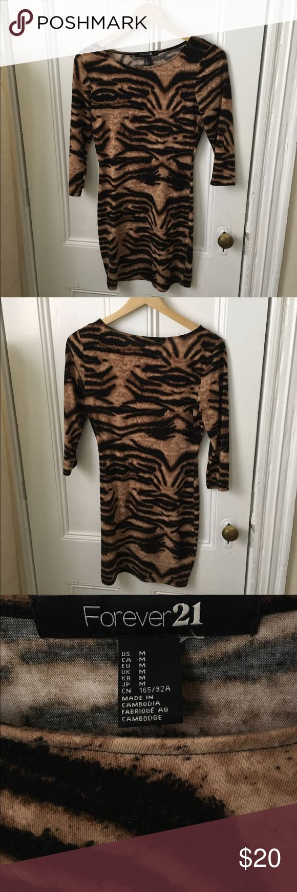 "Tiger Print Dress 3/4 Sleeve Tiger animal print bodycon dress. Tag says medium but I'm a busty small and it looks great on me. 34"" Length 17"" Bust (flat) 14"" Waist (flat). Forever 21 Dresses Long Sleeve"
