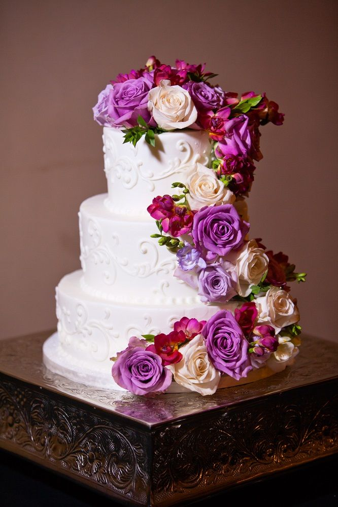 Gorgeous three tier white wedding cake with lavender, purple, magenta and white rose detail on the side | David De Dios Photography | villasiena.cc