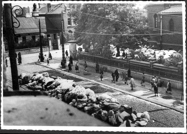 Lodz, Poland, A ghetto street prior to a deportation; bags are stacked on the side of the road.Jews would be deported and gassed