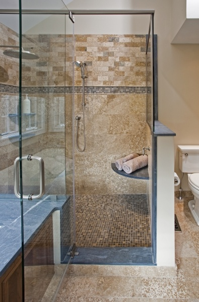 the frameless glass shower enclosure features rustic walnut travertine tile a stone mosaic accent band