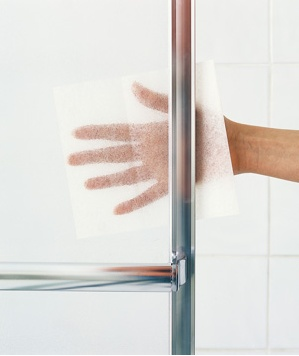 """Remove obstinate soap buildup from glass shower doors by sprinkling a few drops of water onto a used fabric-softener sheet and scrubbing."""