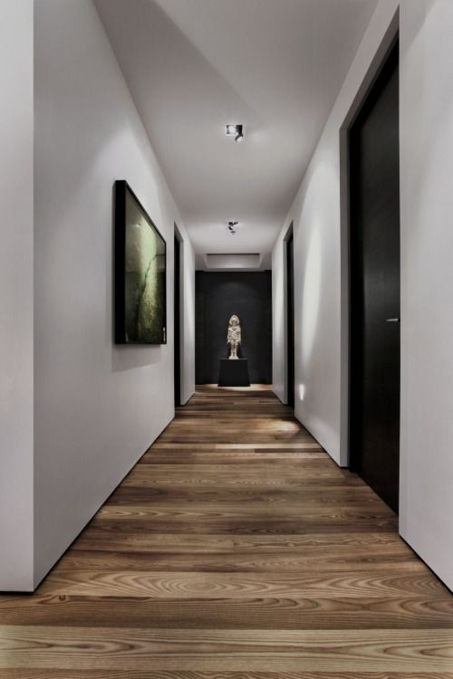 Hallway with white walls and natural wood floors