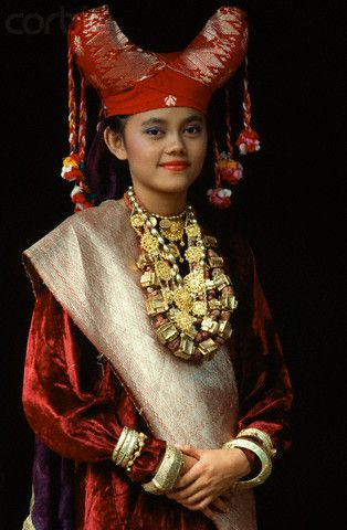 """Minangkabau Woman Wearing Headdress, Indonesia, Sumatra. Buffalo. especially its horns are important cultural symbol in Minangkabau culture. The roofline of traditional houses in West Sumatra, called Rumah Gadang (Minangkabau, """"big house""""), curve upward from the middle and end in points, in imitation of the water buffalo's upward-curving horns. The fabrics of Minangkabau women headdress also folded and formed to imitate the buffalo's horn."""
