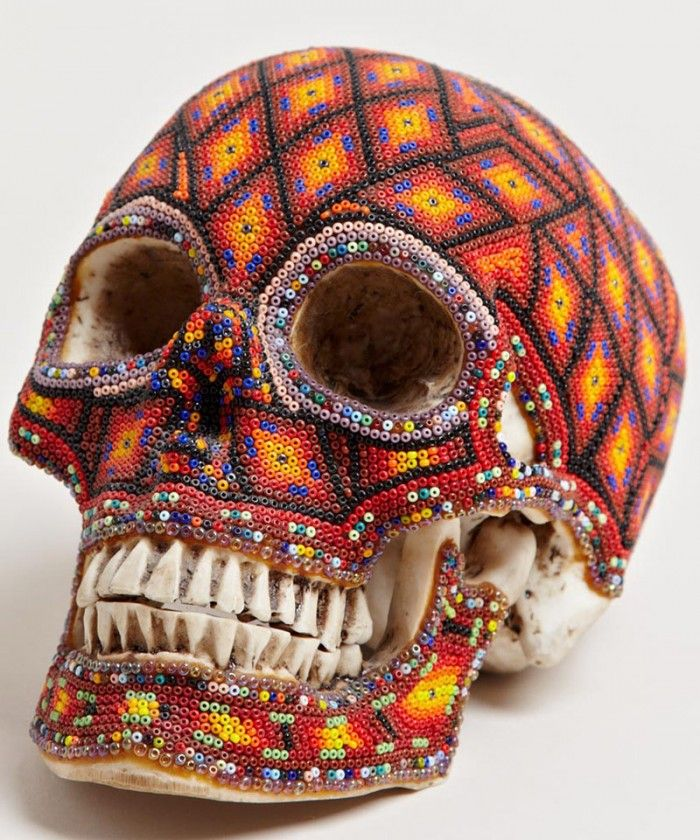 Each of the heavily beaded pieces has been decorated by various artists from the Huichol, using traditional symbols and designs arranged within the patterns, making every skull a completely unique piece of art. The Huichols are decendants of the Aztecs and believe in the Sun God, ancestral spirits and four principal deities – Deer, Corn, Coyote and Eagle. The Sierra Madre Mountains are their home and the Huichol have a long history of creating beaded art, which is a big part of their…