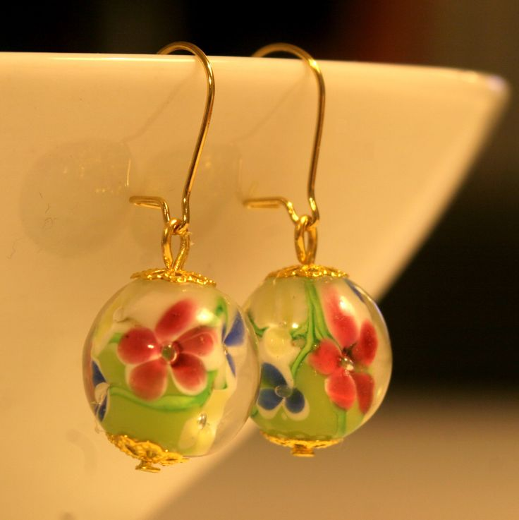 Limenvihreistä lamppuhelmistä tehdyt korvakorut, joissa kullanväriset, nikkelittömät koukut ja koristeosat.