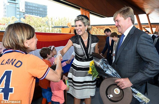 All smiles: Maxima, 45, smiled as she shook hands with a royal enthusiast while Willem-Alexander held a bunch of sunflowers