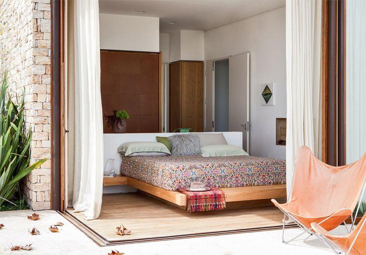 Materiais de toque caloroso, como a madeira, foram escolhidos para trazer aconchego. A cama de freijó lavado parece flutuar, apoiada numa base de alvenaria. Ao fundo do ambiente, os armários têm portas de correr cobertas de couro.