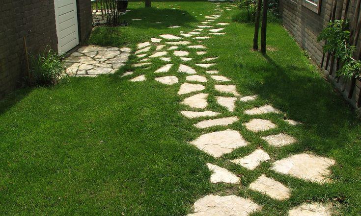 Een pad van stapstenen slingert over het gazon. Het gras groeit tussen de voegen.
