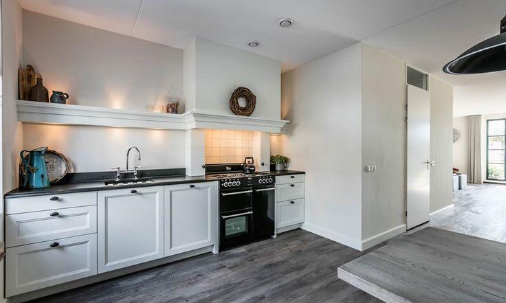Landelijke keuken in rechte opstelling, gekocht bij Keur Keukens in Haarlem. Een witte keuken met fornuis en schouw. Bekijk meer foto's en lees de ervaring van de klant op onze website. #landelijk #wit #keuken #fornuis