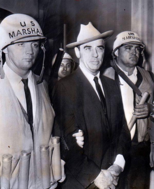 """U.S. marshals escorted Walker after his arrest on the Ole Miss campus on Oct. 1, 1962. In 1962, Walker orchestrated a march of white segregationists at the Ole Miss'. This became known as the Ole Miss' riot. U.S. Army Major General Edwin A. Walker (ret) was an avowed segregationist. """"It will be my purpose now, as a civilian, to attempt to do what I have found it no longer possible to do in uniform."""" On September 26, 1962, Walker went on several radio stations in Miss.: (excerpt) """"Rise...to…"""