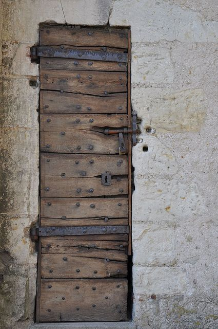 This rough-hewn wooden door with quirky metal locks and fittings makes me curious to find out what is behind it... France