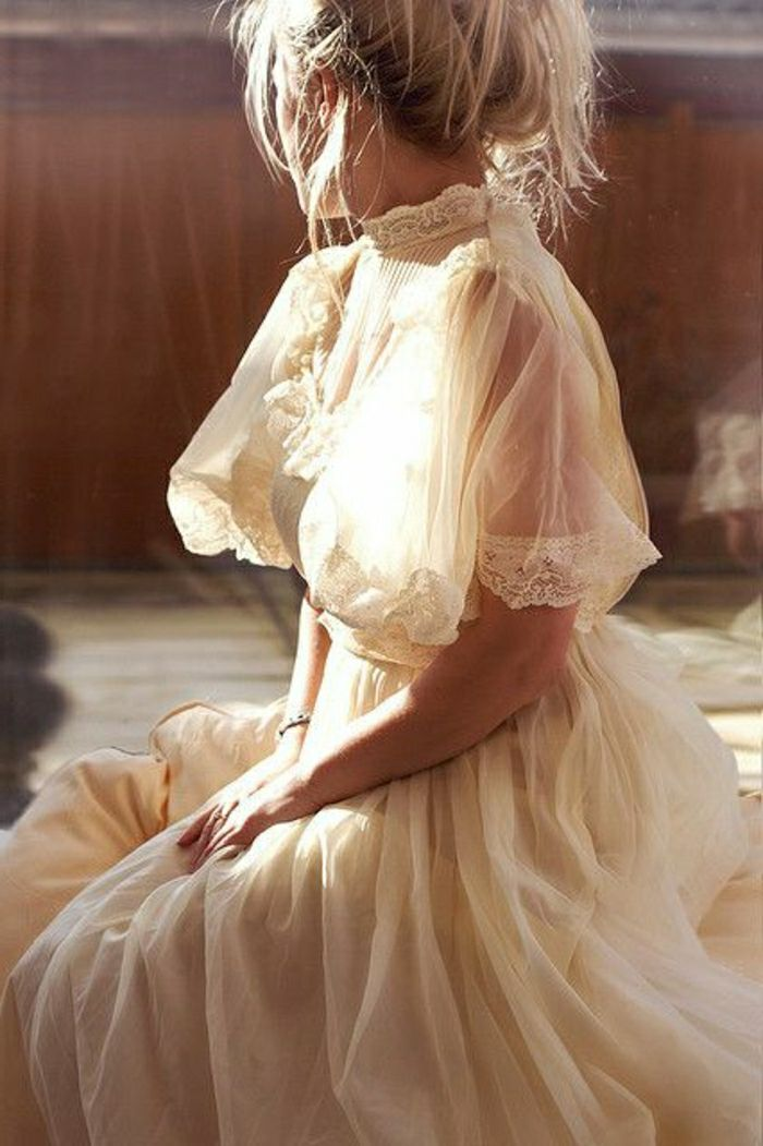 unique wedding dresses, blonde woman sitting down with hands in lap, in a Victorian cream wedding dress with lace and sheer short sleeves, messy hair bun
