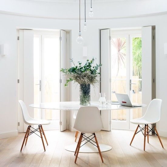 This elegant and serene dining room shows just how successful decluttering can be! Take white chairs, white table and white interior shutters, team with a pale wood floor and you've got the ultimate in pared-back style. We love! Foliage adds a touch of softness.