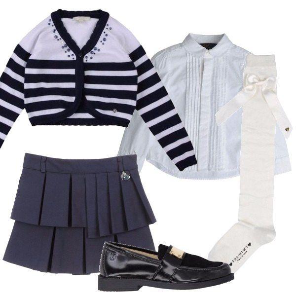 Outfit ispirato al look collegiale, composto da gonna a pieghe blu, camicetta bianca a maniche lunghe e cardigan a righe bianche e blu. Per completare, stringata nera da indossare con calzino alto con fiocco laterale.