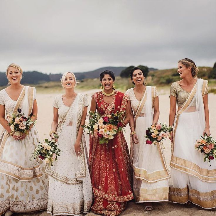Bridesmaids in white dresses, with the bride in red. Great color combination for one