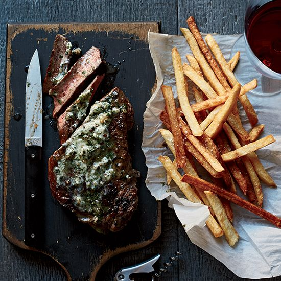 Strip Steak Frites with Bearnaise Butter | This brilliant take on steak frites is a specialty of chef Andrew Carmellini. He tops seared strip steaks with a butter infused with tarragon, shallots and vinegar—key ingredients in béarnaise sauce—and serves them with tangy French fries made with vinegar-brined potatoes.