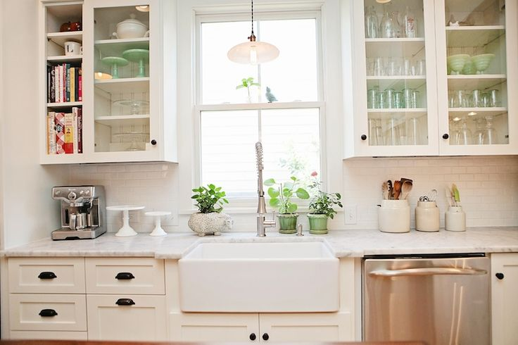 source: New Old  Fabulous kitchen with white cabinets accented with oil-rubbed bronze cup hardware alongside Carrara Marble countertops and a white mini subway tiled backsplash. The kitchen features a vintage pendant flanked by glass-front cabinets over stainless steel dishwasher beside the farmhouse sink with modern spray faucet.