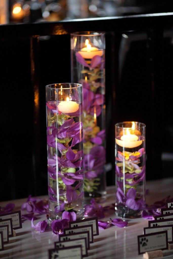 orchid centerpiece.....especially like the orchids scattered around the vases carrying the color down to the table.