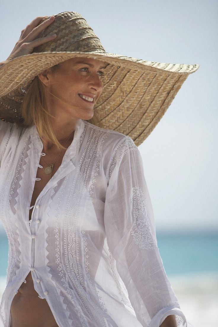 White shirt cum cover up with big straw hat for beach.