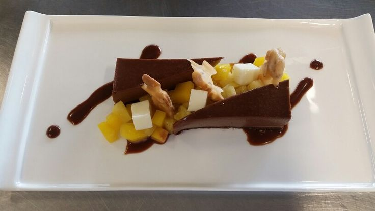 """Snickers"" dessert: chocolate mousse with caramel ganache, peanut brittle, peanut milk jelly and sautéed pineapple and mango salad"