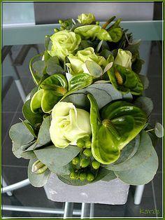 centre de table avec anthurium, roses, hypericum, et autres fleurs/feuillage que je ne peux identifier