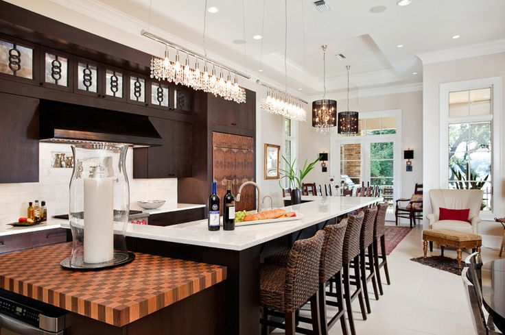Galley-style kitchen with Calacatta Gold marble island, checkerboard cherry and walnut block. Graphic burled walnut veneer covers the Sub-Zero fridge. James R. Moder chandeliers | In Detail Interiors