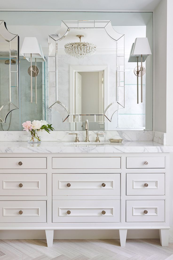Dream Master Bathroom with custom designed furniture style vanity, thick marble countertop and mirror on mirror detail. Urban Electric Melissa Sconce, Mirror Image, Rohl Faucet. Trillion Semi-Flush Mount. White Glamorous Bathroom. Crystal chandelier, herringbone stone floor. Interior design and detailing by SHOPHOUSE Interiors.