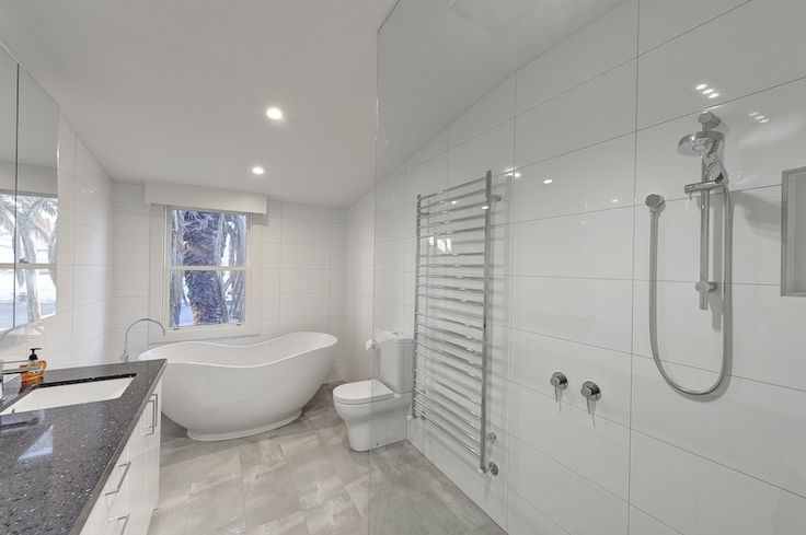 Bathroom enhanced with floor to ceiling tiles.