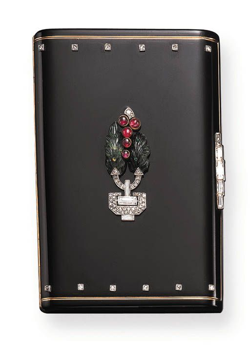 AN ART DECO DIAMOND, GEM-SET AND BLACK ENAMEL VANITY CASE, BY CARTIER Of rectangular outline in black enamel, centering upon a carved emerald, cabochon ruby and rose-cut diamond foliate motif, with a baguette and rose-cut diamond base, enhanced by rose-cut diamond borders and a baguette-cut diamond thumbpiece, opening to reveal a mirror, a covered compartment and a lipstick holder, mounted in 18K gold, circa 1925