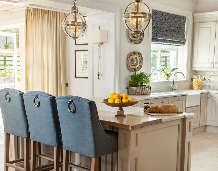 Polished nickel lanterns add a glamorous touch to this hand-painted kitchen. Designed by Missi Gray Interior design.