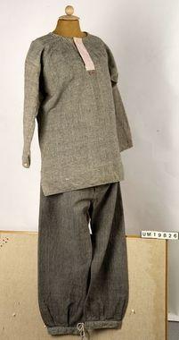 """Skjorta 1910-1920  Smögen. Mansskjorta i kypert med inslag av grått ullgarn och varp av vit bomull. Sydd av raka tygstycken och med kil under ärmen. Sprund i sidorna. Knäppt med en benknapp i halsen och på ärmarna. Halsen och sprundet förstärkt med röd och vitrandigt bomullstyg. Märkt: """"R.H."""" - broderat i kedjestygn med rött bomullsgarn under halssprundet. Lagad bl.a. på ryggen. Sliten och smutsig. Tröjan är kanske ett arv från brukarens far."""