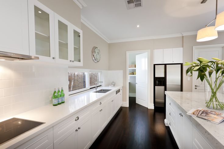Beautiful dark timber floors make a lovely contrast against this mostly white kitchen.