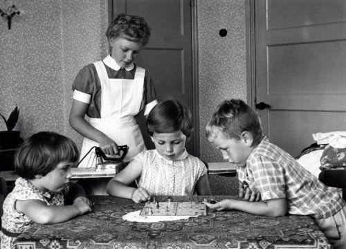 Gezinszorg : Terwijl drie kinderen aan tafel op het tafelkleed een potje `Mens   Erger Je Niet` zitten te spelen staat achter hen een jonge gezinshulp te strijken   met een strijkplank en strijkijzer. Nederland, Arnhem, 30 juni 1958.