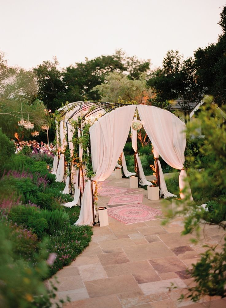 An arched structure entwined with greenery and draped with ivory linens led guests to the garden reception via pink Persian-style rugs for a bohemian-inspired reception entrance. #WeddingEntrance Photograph by: Elizabeth Messina. Read More: https://www.insideweddings.com/weddings/spring-garden-wedding-in-montecito-california/277/