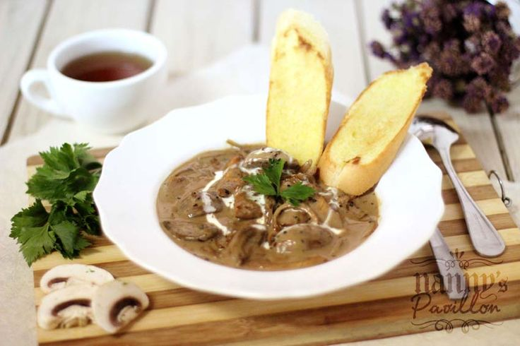 Chicken Stroganoff. Old-classic dish of sauteed pieces of chicken breast in herb creamy sauce, served with toasted french baquette.